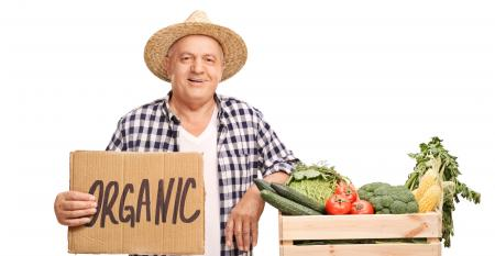 Man holding sign that reads 'organic' standing next to basket filled with vegetables