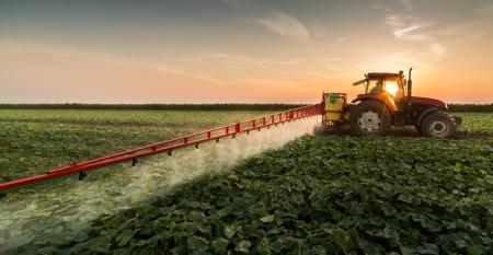 farmer spraying pesticides on field